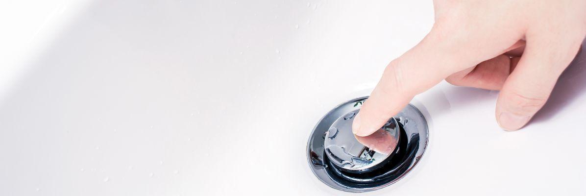 osoba wciska korek klik-klak w umywalce