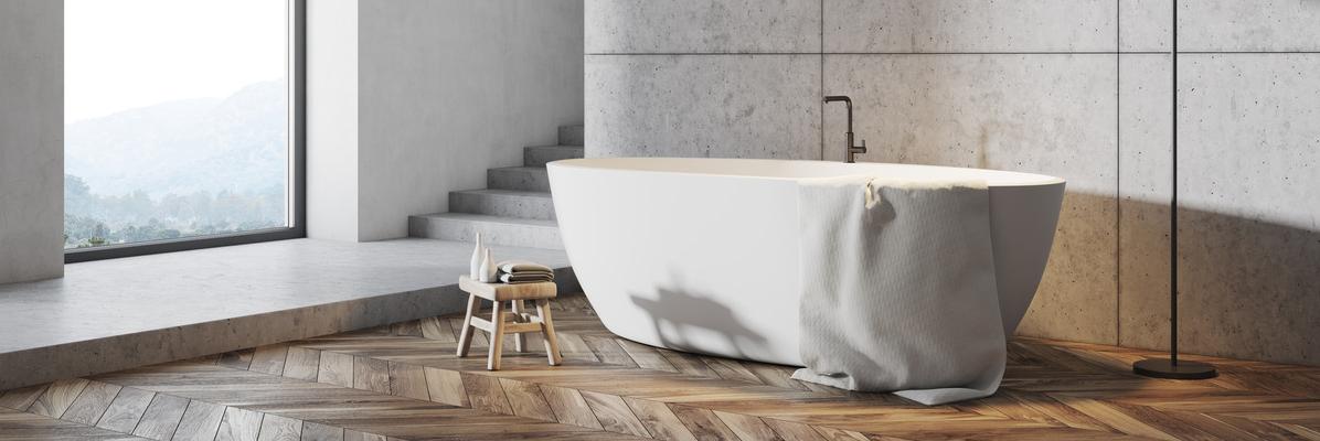wolnostojąca wanna w łazience z drewnianą podłogą i betonowymi ścianami